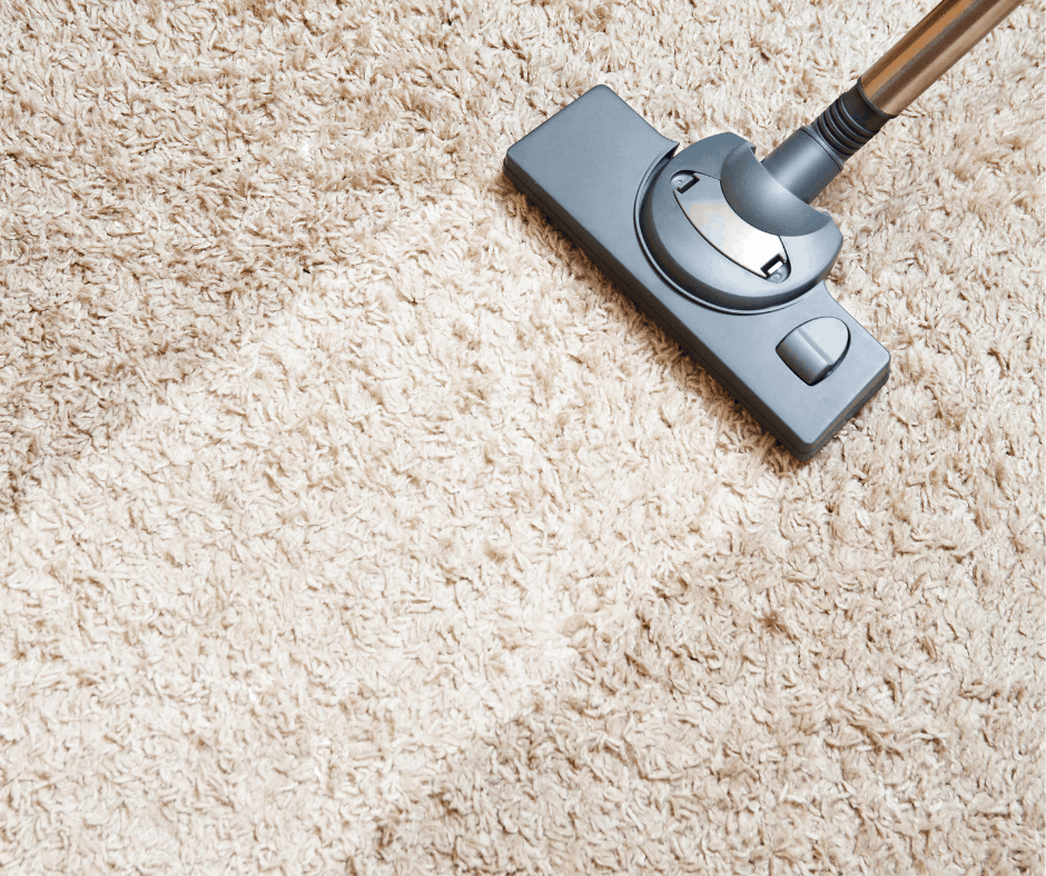 Vaccuum cleaning a white carpeted floor